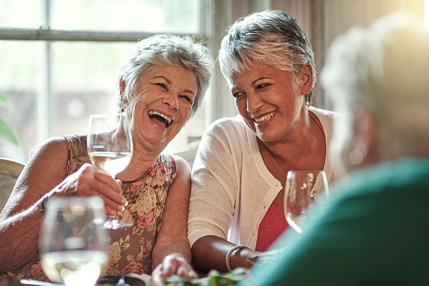 three senior women laughing while eating lunch at a restaurant